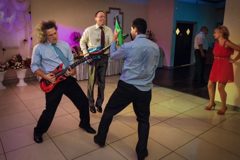 Goście bawią się dmuchanymi gitarami