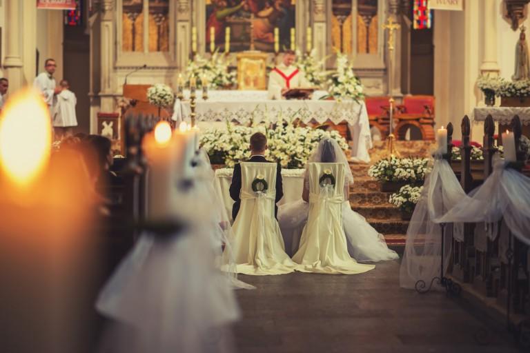 Para młoda, zapalone świece w kościele