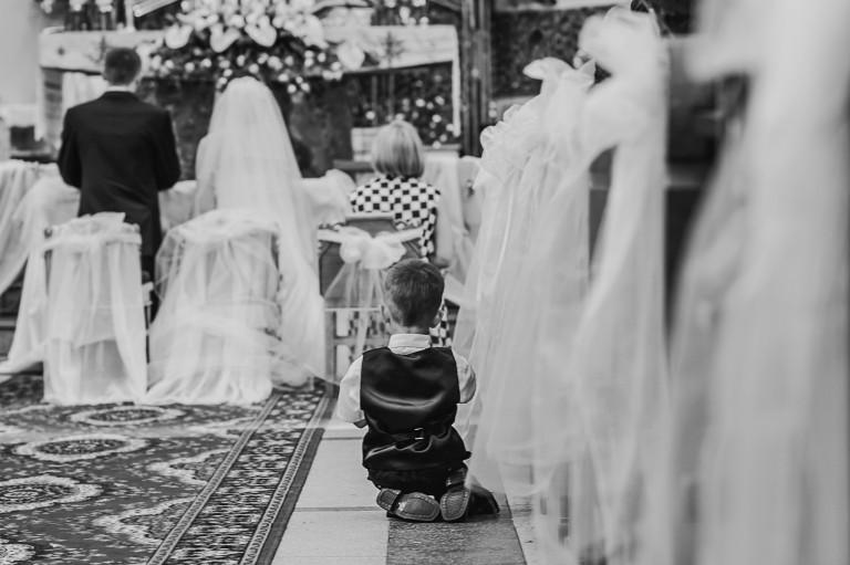 Młody członek rodziny w trakcie mszy