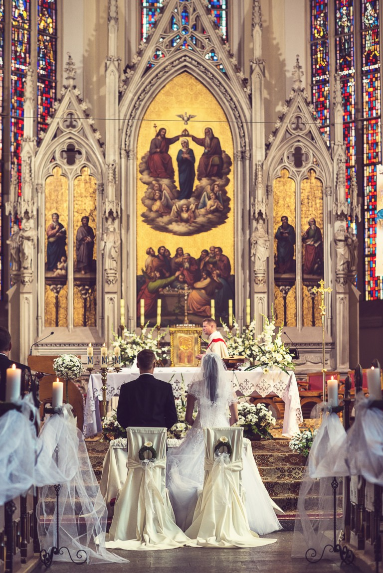Para młoda w trkacie ślubu przed ołtarzem