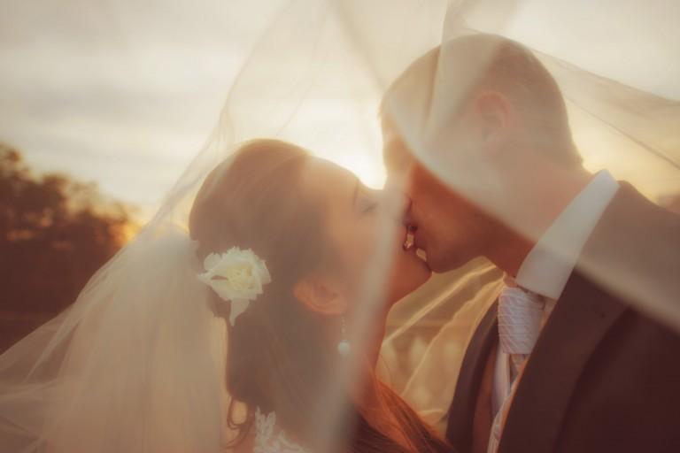Pocałunek młodej pary pod welonem