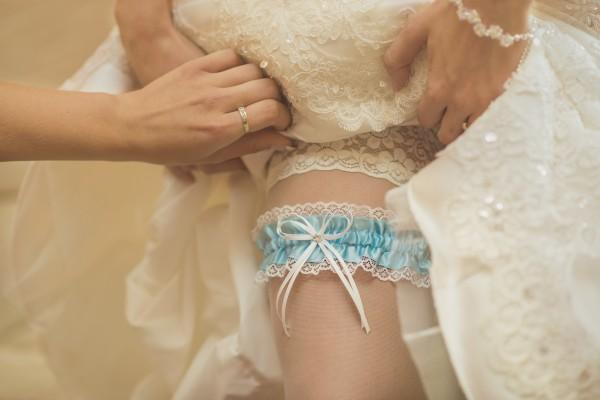 Zakładanie niebieskiej podwiązki, detale ślubne, pończochy
