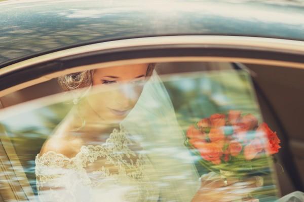 Kolorowy portret Panny Młodej wysiadającej z samochodu, z odbiciami w szybie