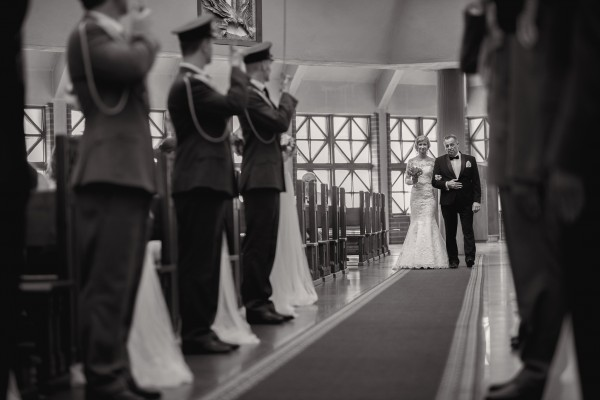 Tata prowadzi swoją córkę do ślubu, żołnierze stoją na baczność