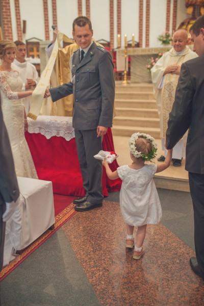 Dziewczynka niesie obrączki na poduszce w kościele