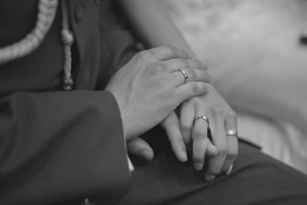 Para młoda trzyma się za ręce w kościele, widać ich obrączki