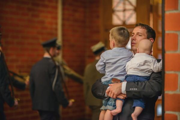 Ojciec z dwójką dzieci w trakcie mszy ślubnej w kościele