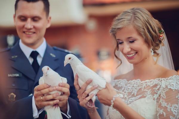 Pan i Pani Młoda trzymają białe gołąbki