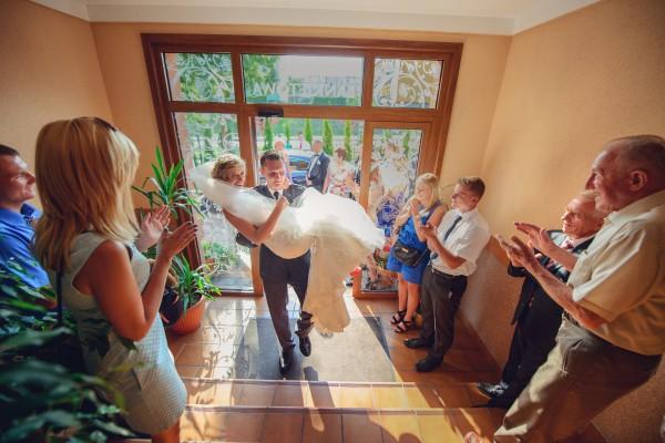 Pan Młody przenosi żonę przez próg sali weselnej