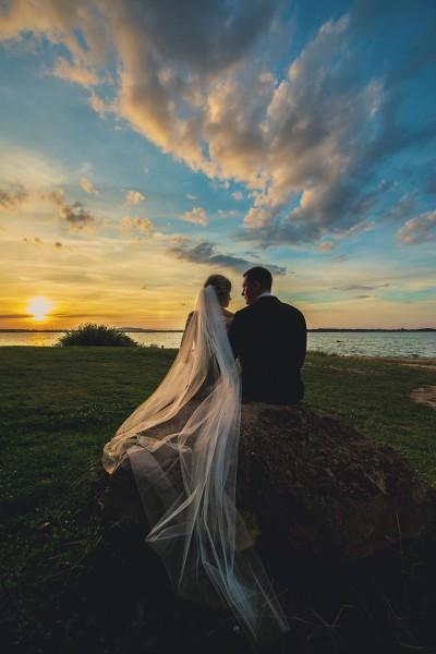 Para wpatrzona w jezioro, piękny i długi welon oraz kolorowe niebo zachodzącego słońca